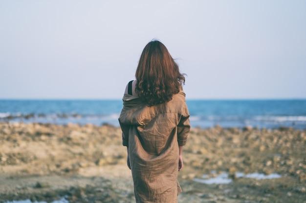 Una bella donna asiatica che cammina sulla spiaggia in riva al mare