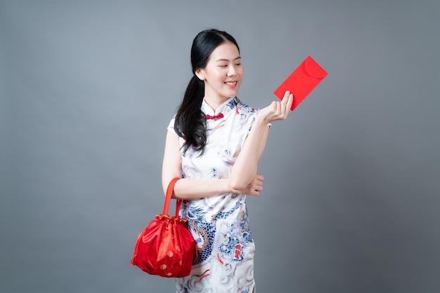 Bella donna asiatica indossa abiti tradizionali cinesi con busta rossa o pacchetto rosso su sfondo grigio