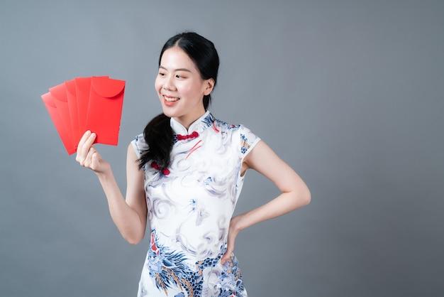 Bella donna asiatica indossa abiti tradizionali cinesi con busta rossa o pacchetto rosso