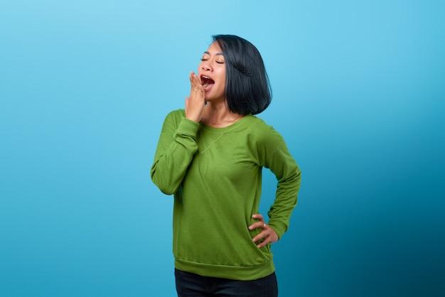 Bella donna asiatica che indossa abiti casual cercando sonnolenza e coprendo la bocca con la mano