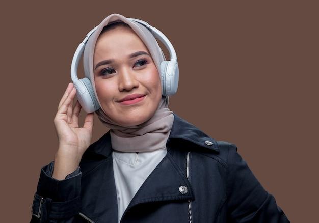 La bella donna asiatica che indossava l'hijab stava ascoltando musica usando cuffie wireless con un'espressione sorridente