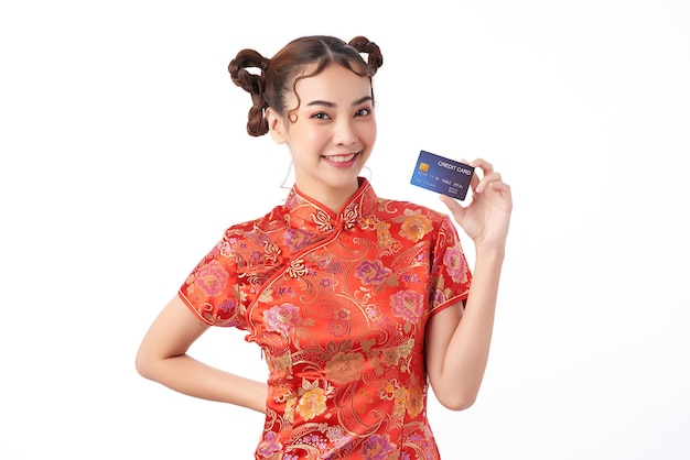 Bella donna asiatica che indossa il tradizionale abito qipao cheongsam che mostra la carta di credito per i concetti di acquisto del capodanno cinese,