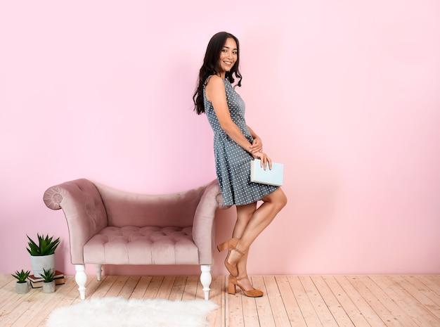 Bella donna asiatica con libro vicino alla parete colorata