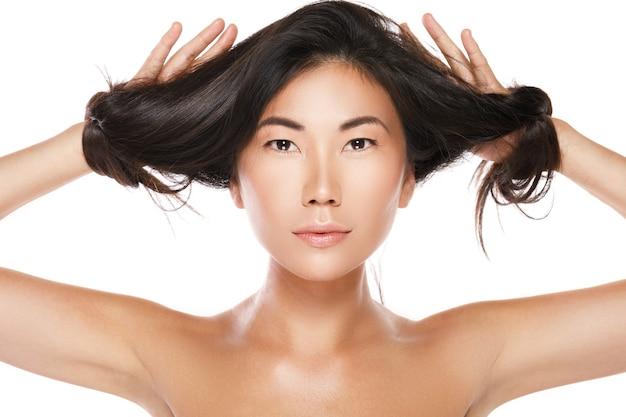 Bella donna asiatica con capelli neri sani sul muro bianco