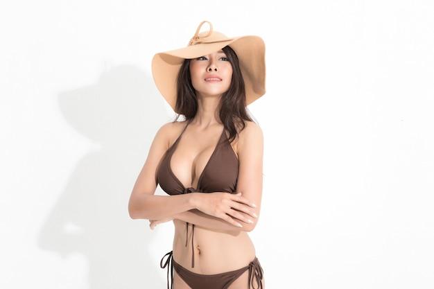Bella donna asiatica con lunghi capelli castani che indossa abito bikini marrone e cappello per il sole isolato su sfondo bianco e ombra.
