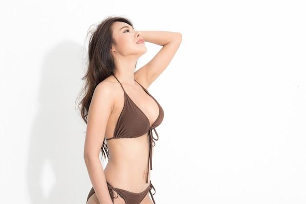 Bella donna asiatica con lunghi capelli castani che indossa un bikini marrone sfondo bianco e ombra.