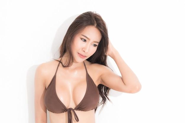 Bella donna asiatica con lunghi capelli castani che indossa un bikini marrone isolato su sfondo bianco e ombra.