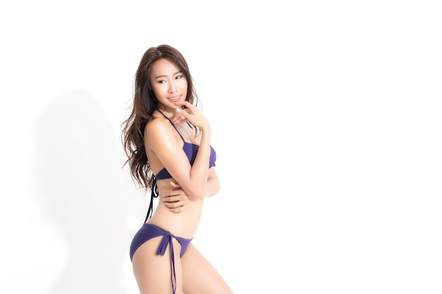 Bella donna asiatica con lunghi capelli castani che indossa un bikini viola vestito isolato su sfondo bianco e ombra.