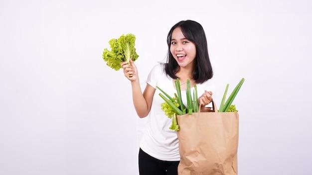 Bella donna asiatica con un sacchetto di carta di verdure fresche e tenendo la lattuga fresca con superficie bianca isolata