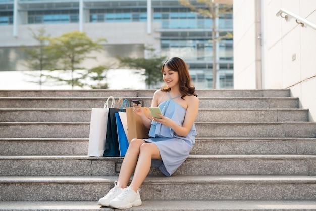 Bella donna asiatica con borse della spesa seduta sulle scale mentre guarda lo smartphone e tiene la carta di credito.