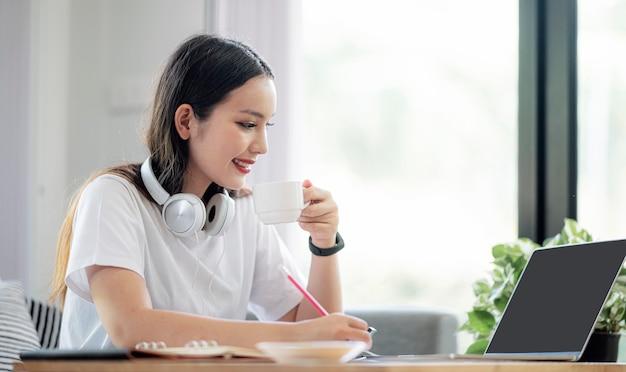 Bella donna asiatica che lavora con il computer portatile mentre sedendosi a casa.