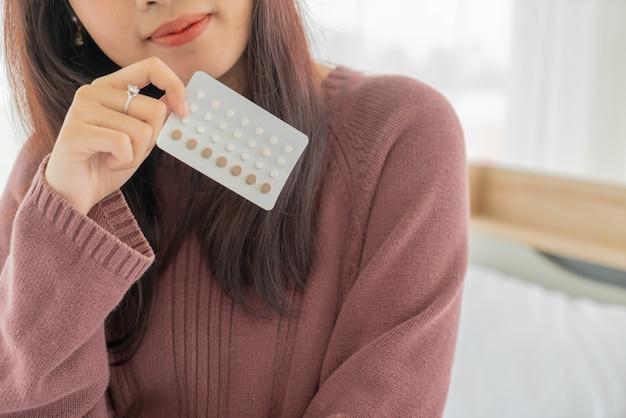 Belle donne asiatiche che tengono la pillola anticoncezionale