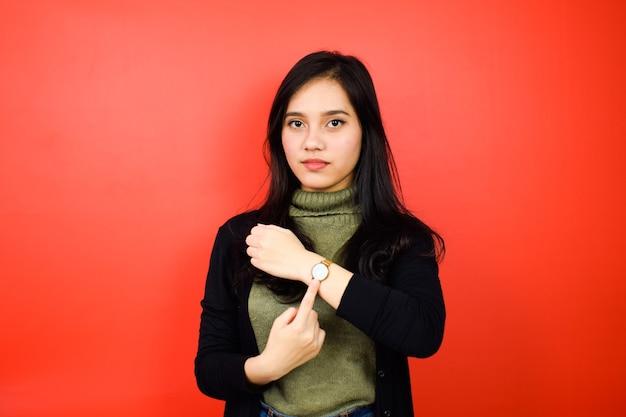 Belle donne asiatiche che usano un maglione nero che puntano all'orologio con sfondo rosso isolato