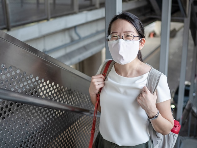 Belle donne asiatiche indossano una maschera medica monouso ogni volta fuori casa, come una nuova tendenza normale e l'autoprotezione