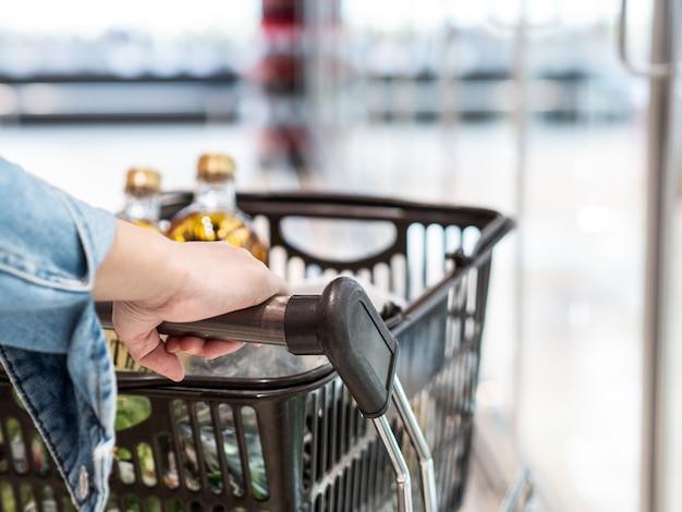 Le belle donne asiatiche indossano la maschera con il carrello nel supermercato nel centro commerciale o nel grande magazzino, si distinguono dalle altre persone per mantenere la distanza sociale di sicurezza, come nuovo concetto di stile di vita normale