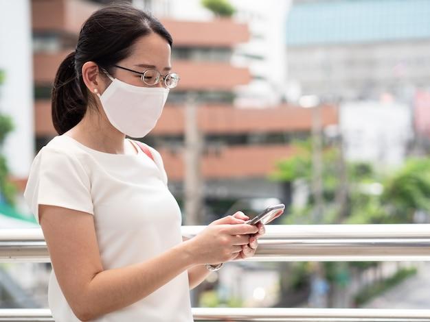 Belle donne asiatiche che indossano una maschera medica usa e getta, utilizzando lo smartphone in un'area pubblica, lungo la strada o nel centro città, come nuova tendenza normale e autoprotezione contro l'infezione da covid19.