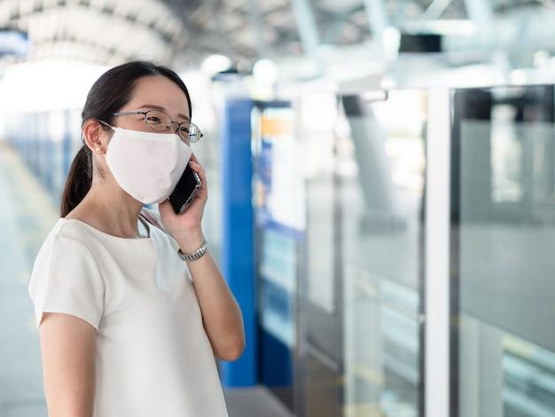 Belle donne asiatiche che indossano la maschera medica usa e getta, utilizzando lo smartphone in attesa della metropolitana alla piattaforma della stazione ferroviaria, come nuova tendenza normale e autoprotezione contro l'infezione da covid19.