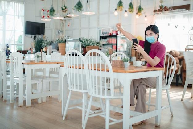 Belle donne asiatiche che indossano maschere lavorano online in un bar vende liberamente prodotti online, si diverte a lavorare a casa durante l'infezione da covid-19.