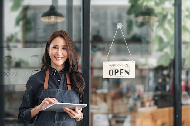 Bella donna asiatica giovane barista in grembiule che tiene compressa e in piedi davanti alla porta del caffè con cartello aperto. concetto di avvio dell'imprenditore.