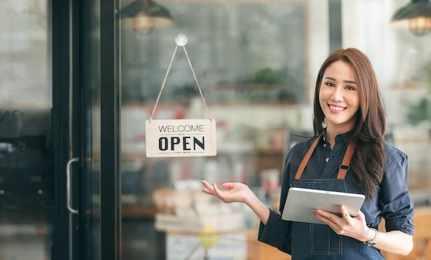 Bella giovane donna barista asiatica in grembiule che tiene compressa e in piedi davanti alla porta del caffè con cartellone aperto. concetto di avvio dell'imprenditore.