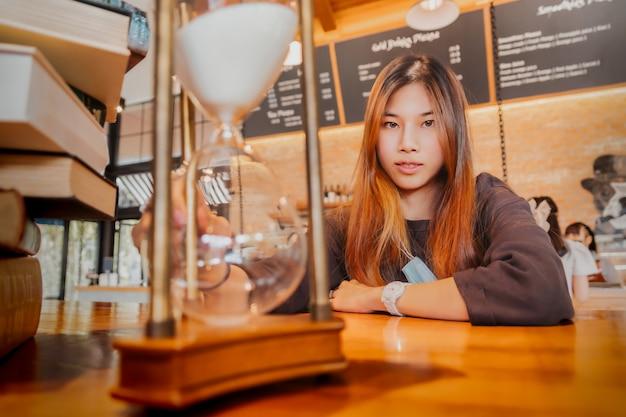 La bella giovane femmina asiatica è seduta davanti a una clessidra che fa il conto alla rovescia con un sorriso per il concetto di tempo rilassante.