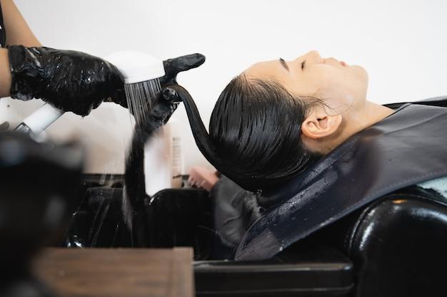 Bella giovane donna asiatica che ha un trattamento per la cura dei capelli e un servizio di lavaggio dei capelli al parrucchiere.
