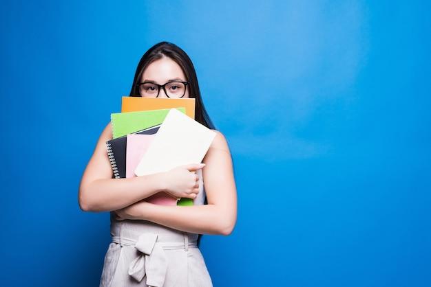 Bello libro di lettura asiatico della giovane donna isolato sulla parete blu