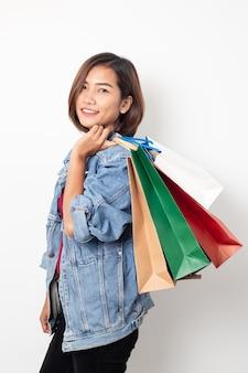 Sacchetti della spesa sorridenti della tenuta della bella giovane donna asiatica