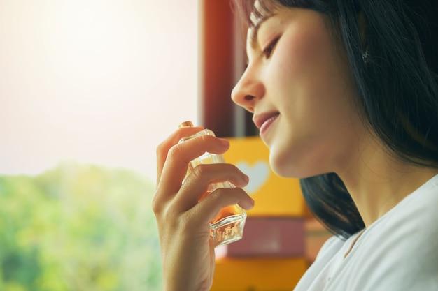 Bella giovane donna asiatica con una bottiglia di profumo in casa, primo piano