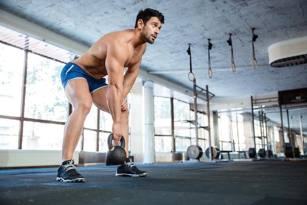 Bellissimo atleta che indossa pantaloncini blu che sollevano la palla del bollitore