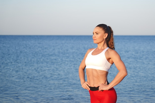 Bella donna atleta in abiti sportivi rossi in posa sullo sfondo del paesaggio di mare. allenamento mattutino in riva al mare, stile di vita sano