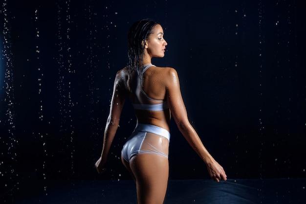 Bella ragazza caucasica atletica con una figura perfetta è in piedi sotto l'acqua.