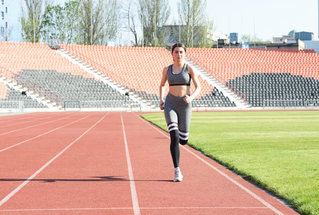 Bella ragazza atletica che corre intorno allo stadio