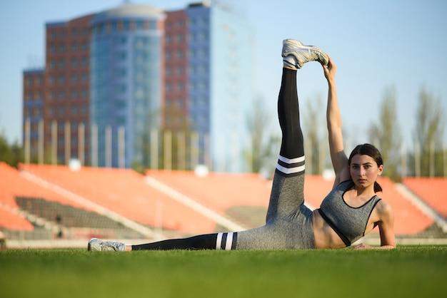 Bella ragazza atletica in fase di riscaldamento prima di un duro allenamento allo stadio