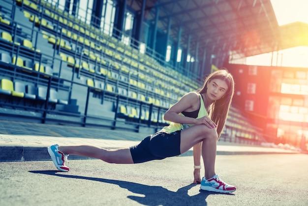 Bella signora atletica che fa esercizi di stretching mattutino. concetto di allenamento quotidiano