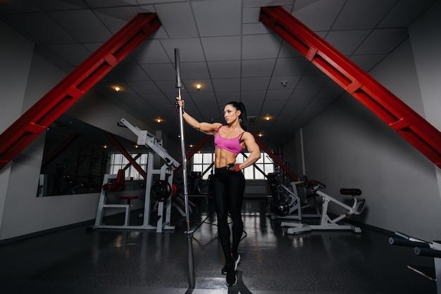 Ragazza sexy bella e atletica che posa in palestra dopo un duro allenamento. fitness, bodybuilding.