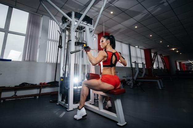 Una ragazza sexy bella e atletica si allena e fa fitness in palestra. fitness, bodybuilding.