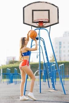 Bella ragazza snella atletica in pantaloncini corti che tengono una palla di pallacanestro di estate sul campo sportivo