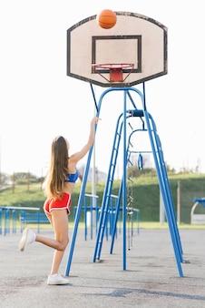 Bella ragazza snella atletica lancia un pallone da basket sul ring del parco giochi in estate in pantaloncini e un top