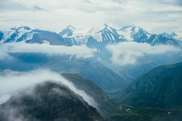 Bellissimo paesaggio alpino atmosferico a grandi montagne innevate con ghiacciaio. nuvole basse tra le rocce nella verde vallata con piccolo fiume. meraviglioso scenario dell'altopiano. volando sopra le montagne sopra le nuvole.
