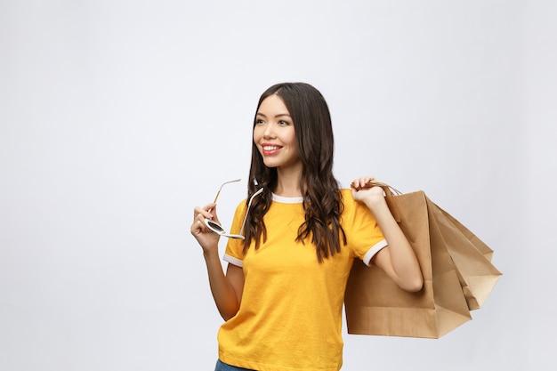 Bella donna asiatica attraente sorriso e tenendo i sacchetti della spesa