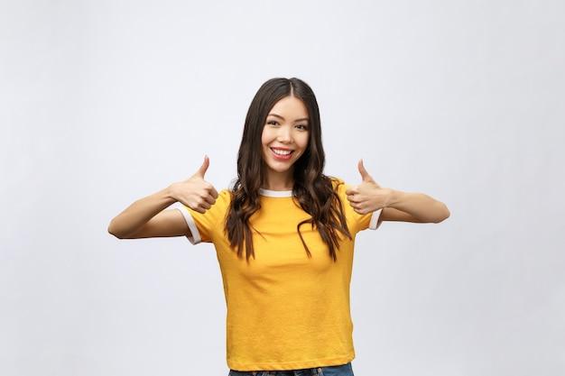 Bello sorriso asiatico attraente della donna e che mostra i pollici in su
