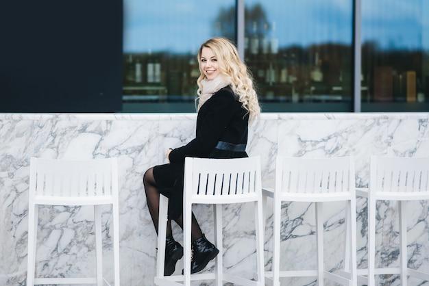 Bella ragazza bionda attraente che si siede dietro un bancone bar in marmo bianco