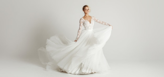 Bella sposa attraente in abito da sposa con gonna lunga lunga