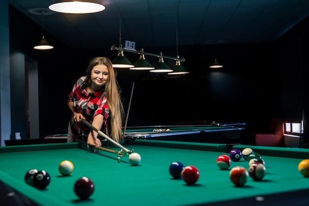 Donna bella e attraente in pub giocando a biliardo