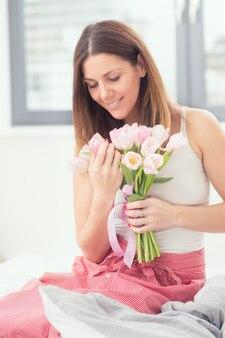 Bella donna attraente seduta sul letto tenendo teneramente in mano un mazzo di tulipani primaverili.