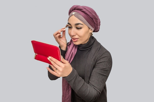 Bella e attraente giovane donna araba che fa trucco. si dipinge gli occhi e si guarda allo specchio.