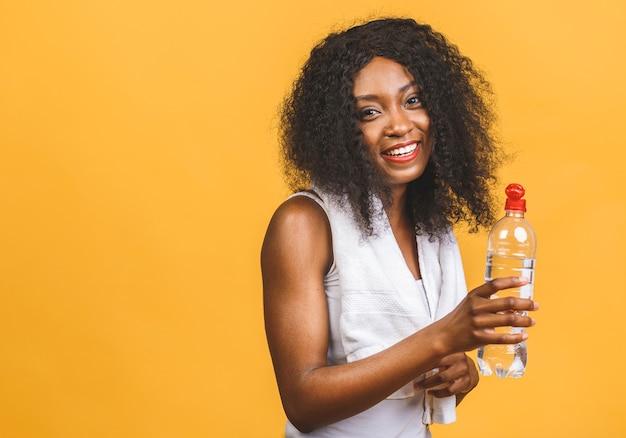 Bella attraente giovane donna nera afroamericana sudata acqua potabile dopo l'allenamento esercizio