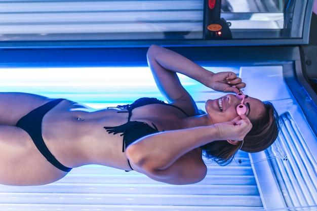Bella e giovane donna attraente che si abbronza nel solarium.