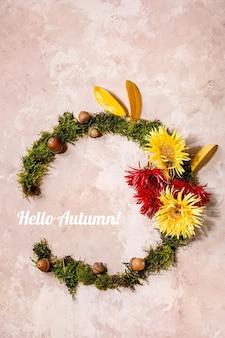Bellissimo layout creativo di composizione ghirlanda botanica autunnale con fiori, muschio e foglie autunnali gialle su sfondo beige. lay piatto, copia spazio. ciao iscrizione autunnale